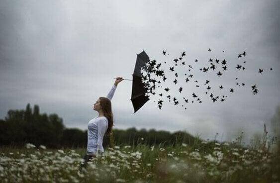 En kvinne med en paraply som forvandler seg til fugler.