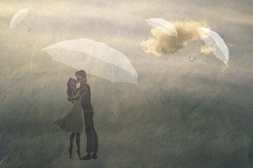 Par som står under en paraply