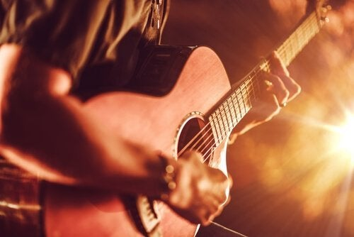 Spiller gitar foran et publikum.