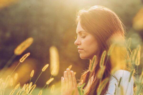 Kvinne som mediterer i en eng