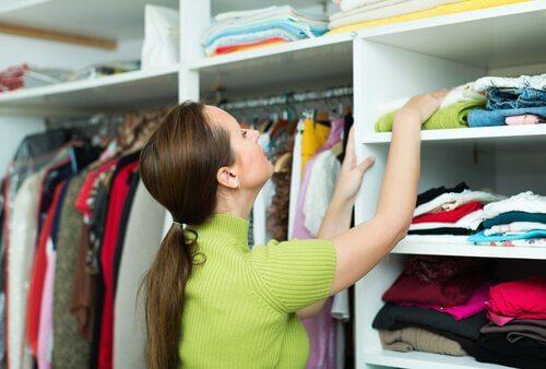 Kvinne organiserer klær i et skap