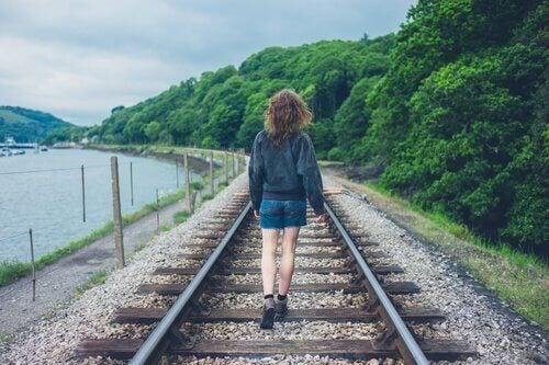 Kvinne går langs togskinne