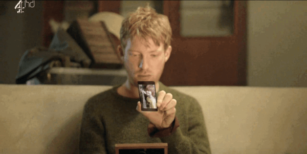 Mann i Black Mirror ser på telefonen sin