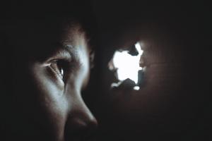 En person som ser gjennom et hull