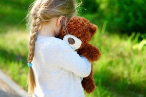 En jentunge som holder en bamse