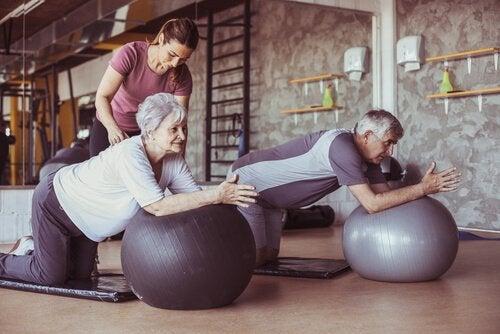 Eldre mennesker trener på yogaballer med trener.