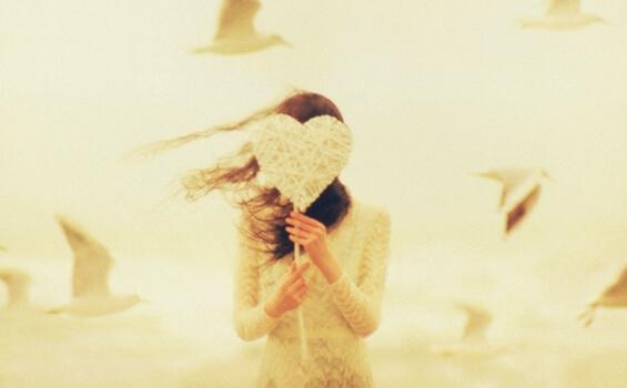 Kvinne med hjerte foran ansiktet
