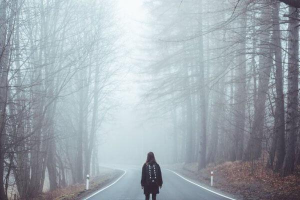 Kvinne går langs grå vei