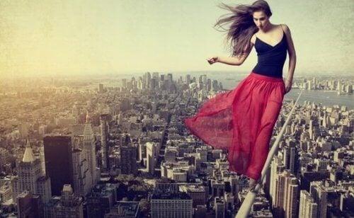 Kvinne med rødt skjørt balanserer på line over en by