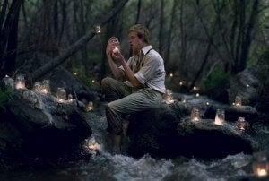 Mann i skogen med et lys