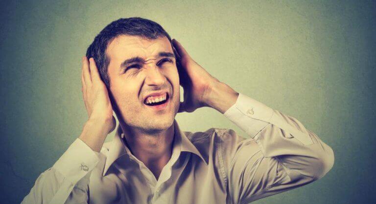 mann som dekker ører