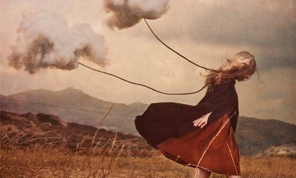 Jente drar skyer i en tråd