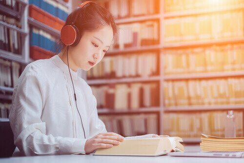 Kvinne lytter til musikk og leser