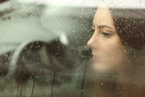 Kvinne bak vindu med regn