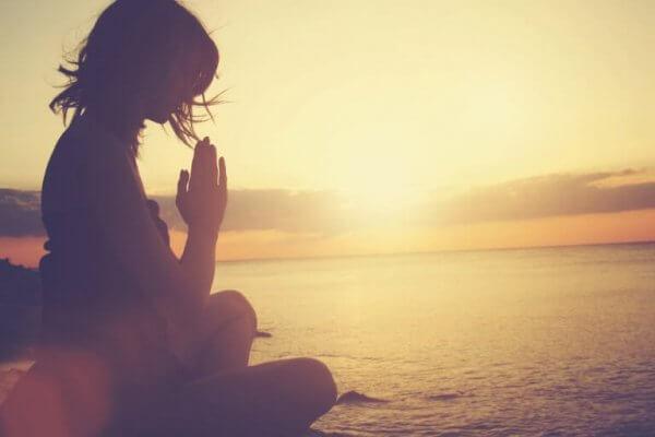 Kvinne mediterer ved vannet