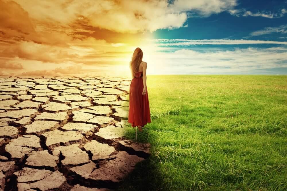 Kvinne står mellom ødemark og grønt gress