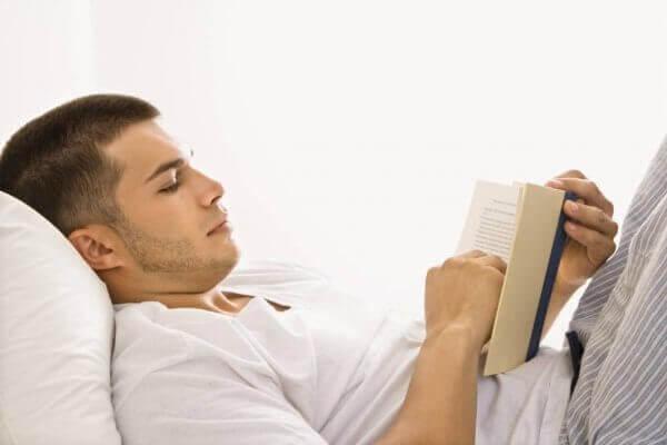 Mann leser i sengen