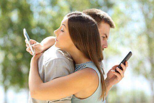 Par klemmer hverandre mens de bruker telefonene sine