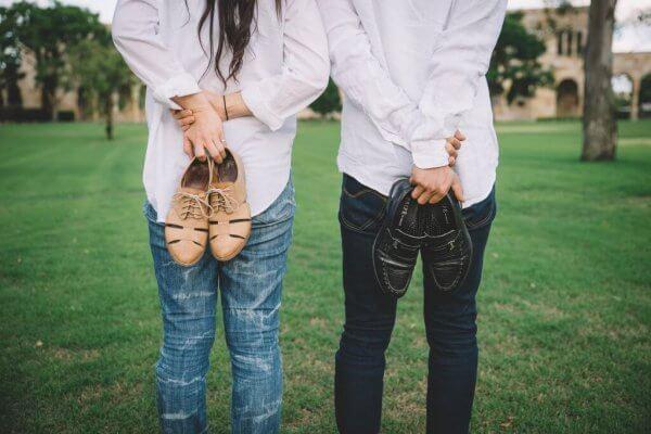 Par som står å holder sko