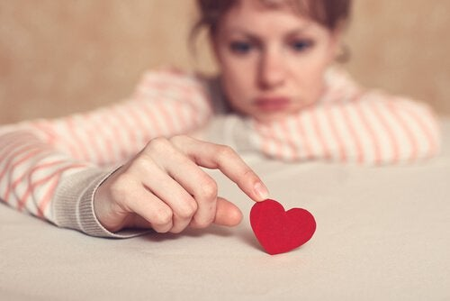 En trist kvinne med et lite rødt hjerte.