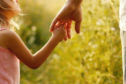 Barn holder hånden til en voksen