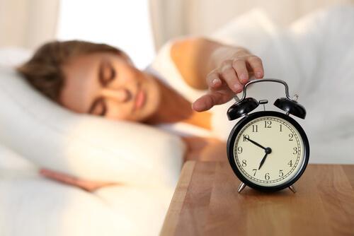 Kvinne skrur av vekkeklokke