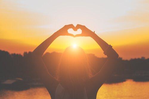 Kvinne lager hjerte med fingrene