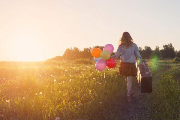 Jente med koffert og ballonger