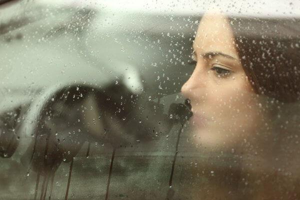 Kvinne ser ut vindu med regn