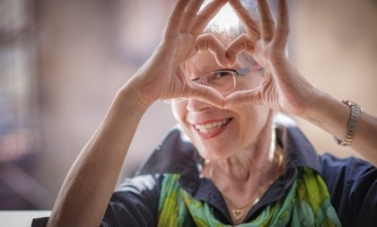 En eldre kvinne gjør et hjerte med hendene sine.