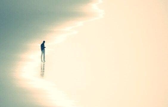 mann på stranden som symboliserer postmoderne ensomhet