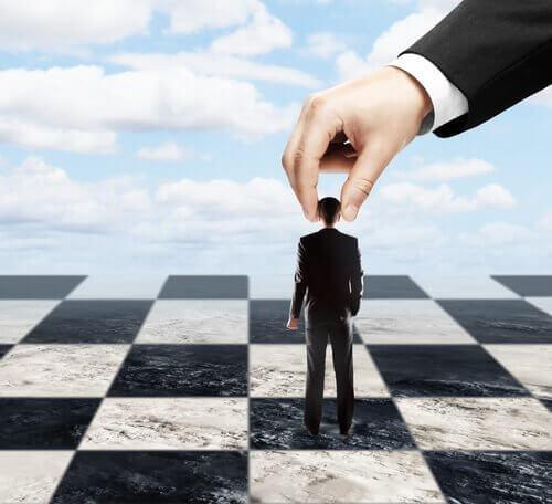 En mann blir manipulert på et sjakkbrett.