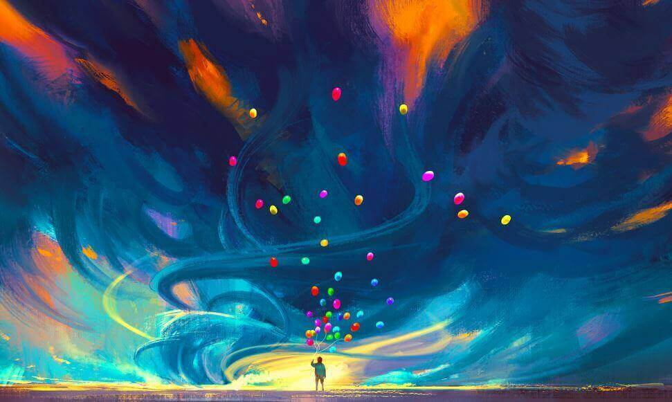 En person som holder en engde fargerike ballonger