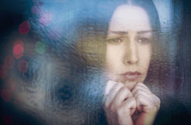 deprimert kvinne ser gjennom vinduet