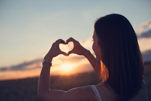 Kvinne lager et hjerte tegn og lærer å elske seg selv