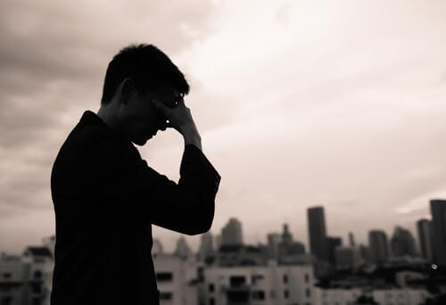 Svart og hvitt profilbilde av en mann som holder hånden for ansiktet. Han ser trist ut.