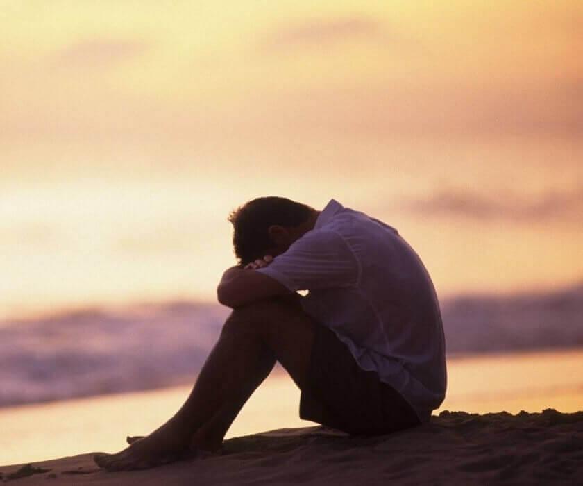 Mann sitter ved havet