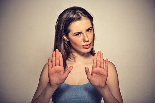 Dame holder hendene opp for å stoppe noe