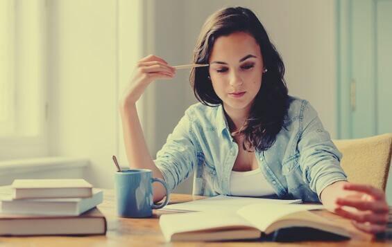 Kvinnelig student leser i bok