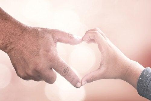 Voksen hånd og barnehånd former hjerte