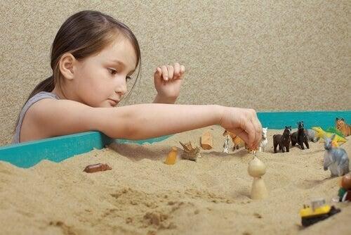 Jente leker med sandkasse
