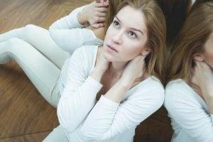 Kvinne som sitter på gulvet og ser opp