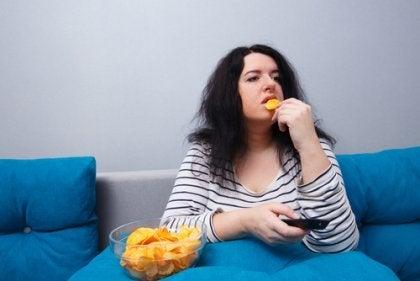 kvinne spiser potetgull i sofaen