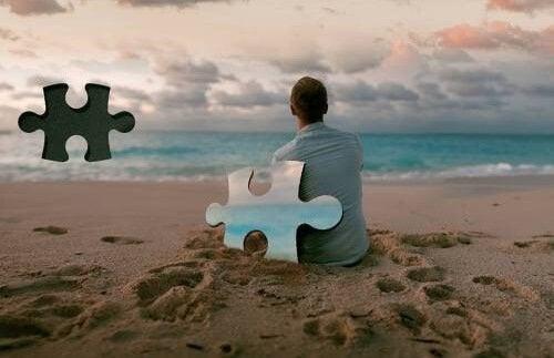 Mann sitter på stranden ved puslespillbrikke