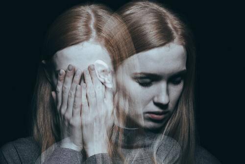 Kvinne holder hodet i hendene