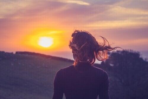 Kvinne i solnedgang vil overvinne fortiden