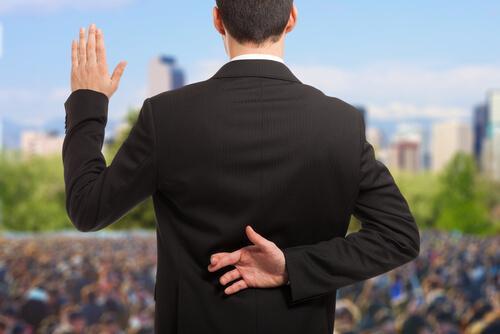 BIldet av en mann i dress forran en stor folkemasse. Han holder opp den ene hånden, som for å love noe, mens den andre hånden krysser fingrene bak ryggen. Et eksempel på post-sannhet.