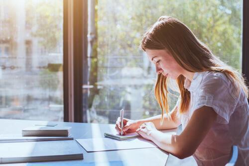 Kvinnelig student skriver notater