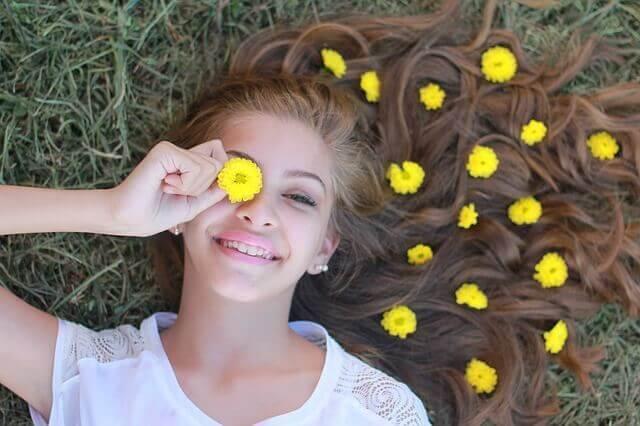 En kvinnelig tenåring har en blomst over øyet.