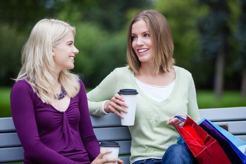To unge kvinner sitter på en benk og drikker kaffe og snakker med hverandre